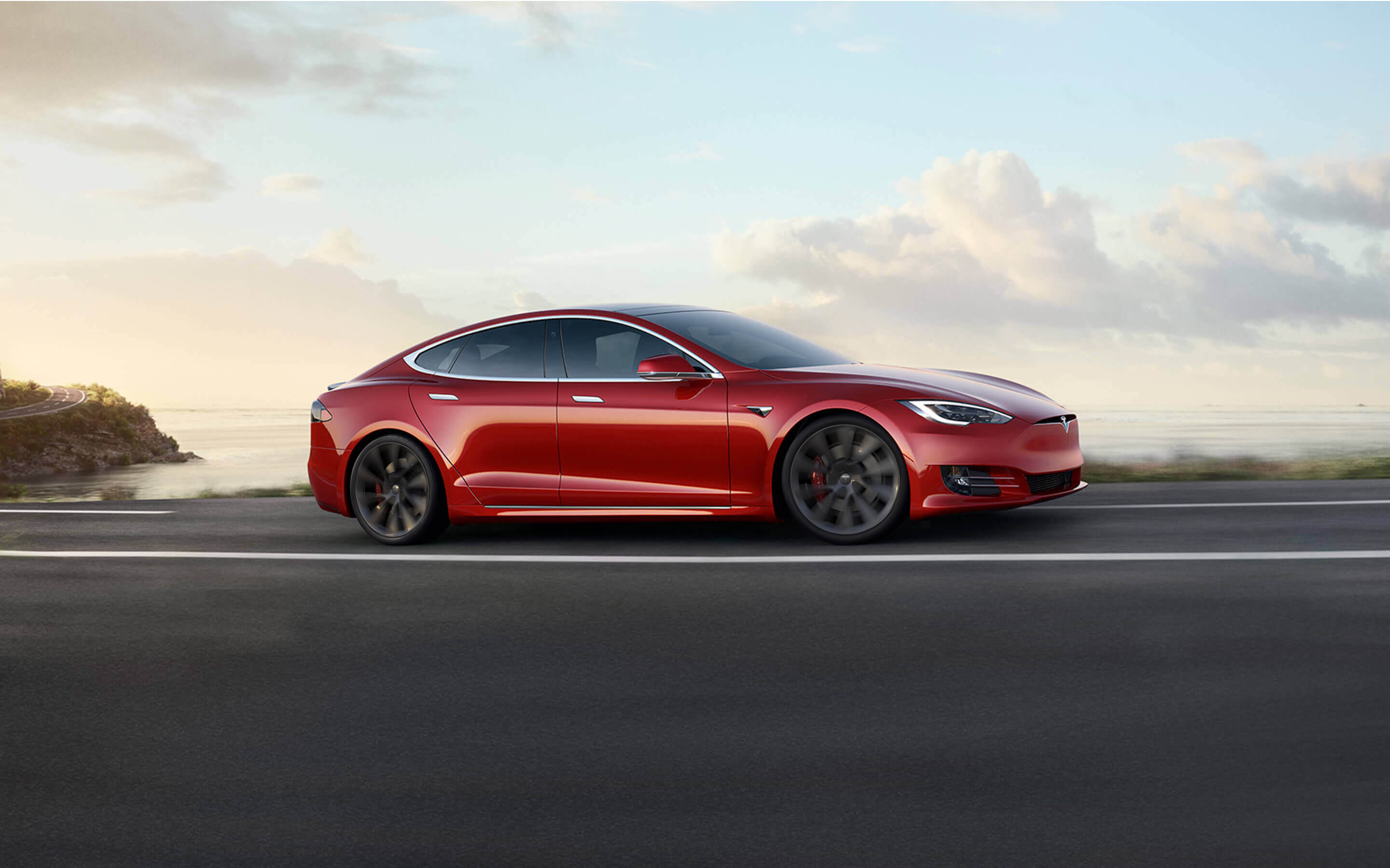 Red Model S accelerating down an oceanside highway