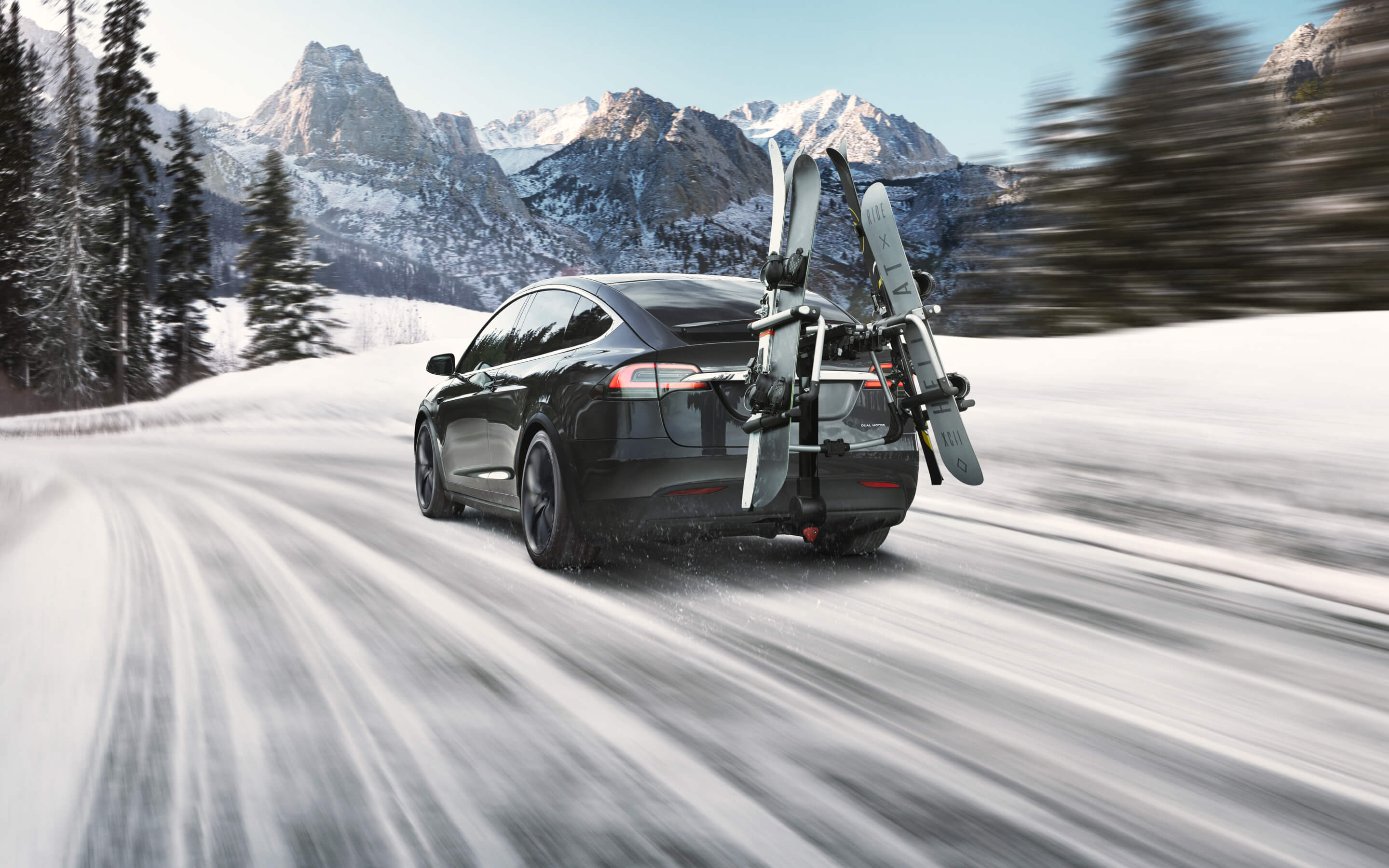 Rear view of black Model X driving through snowy mountains